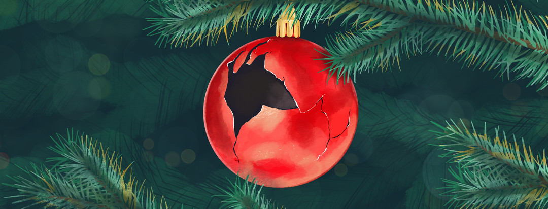 A cracked ornament ball hangs on a Christmas tree.