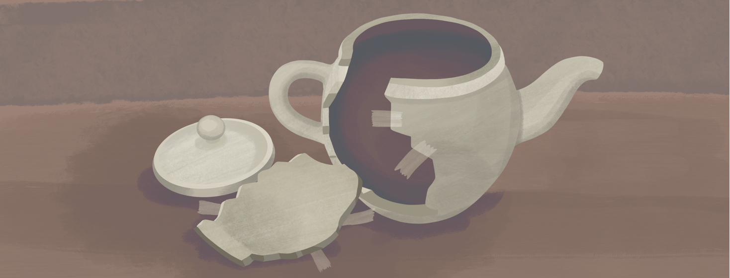 A broken teapot has a piece that has fallen onto the table next to it, while pieces of tape remain on both parts where countless attempts to fix it have taken place.
