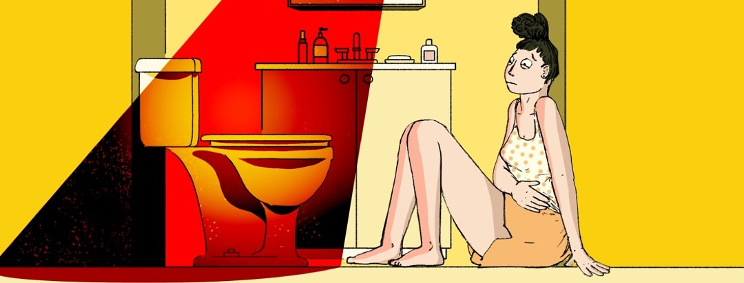 A woman sits uncomfortably on the bathroom floor with her hand over her stomach and staring warily at the toilet in front of her which is illuminated by an evil red light