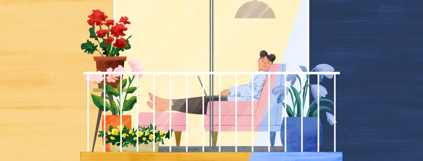 A woman sitting inside on a couch, wistfully looking out glass doors to her outdoor balcony, which is filled with potted plants