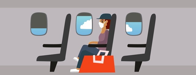A nervous woman on a plane glances down at a red carry on bag