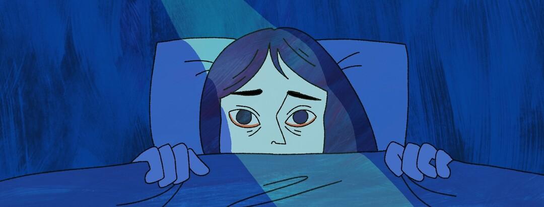 A woman laying awake in bed